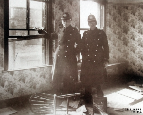Police officers on guard in one of the rooms after the attacks. Note the tin of petrol left by the raisers.