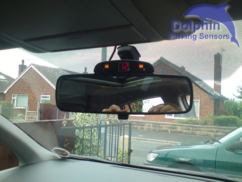 Display mounted on top of the rear view mirror
